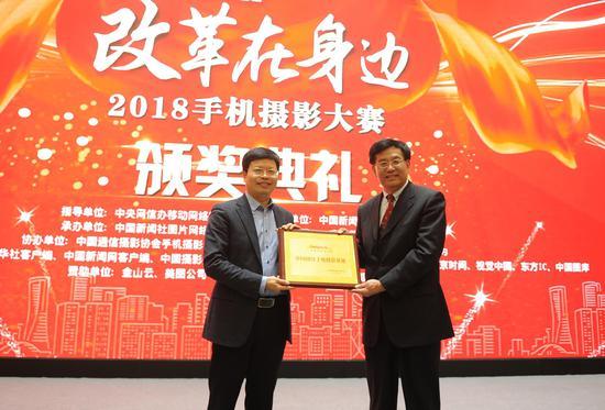 图为:中国新闻社社长章新新为浙江大学中国网络手机摄影基地荣誉授牌。 张茵 摄