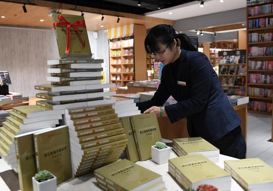 图为:工作人员正在摆放《浙江改革开放40年口述历史》。 王刚 摄