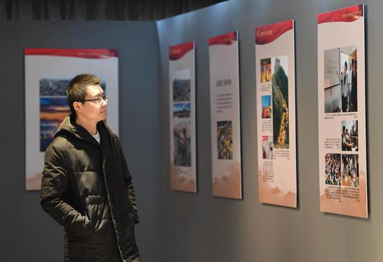 图为:一位市民在观看展览照片。 王刚 摄