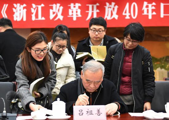 图为:原浙江省省长吕祖善为《浙江改革开放40年口述历史》书签名。 王刚 摄