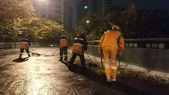 图为:宁波城区道路积雪,城管人员正在清除。 宁波城管提供