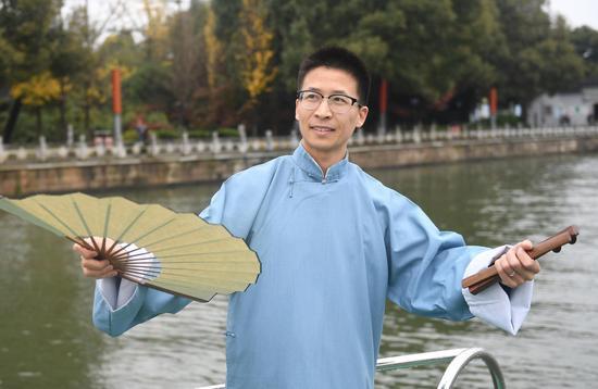 图为:当地从事水利教育工作的吴伟泉表演莲花落。  王刚 摄