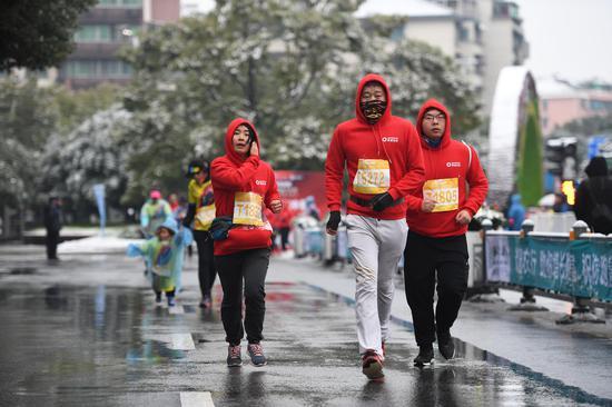 图为:多位市民在雨雪天气奔跑。  王刚 摄