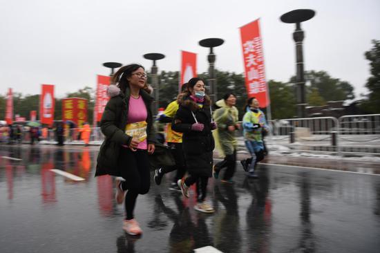 图为:多位市民在马拉松比赛中快速奔跑。  王刚 摄