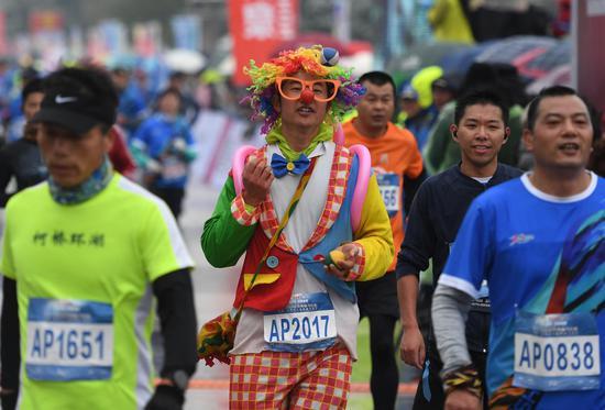 图为:一位跑者扮成小丑形象参加马拉松。  王刚 摄