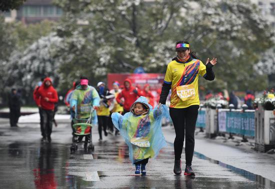 图为:一位市民带着孩子在雨雪天气奔跑。  王刚 摄