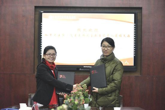 图为:Ms.Xuan与文海实验学校副校长郭莹莹签订中加教育交流合作备忘录。