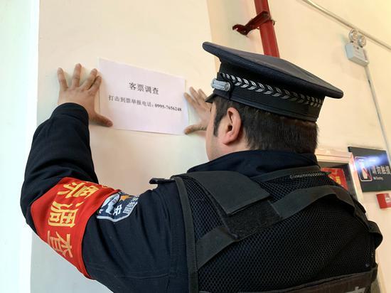 吐鲁番站派出所民警张贴打击倒票举报电话。