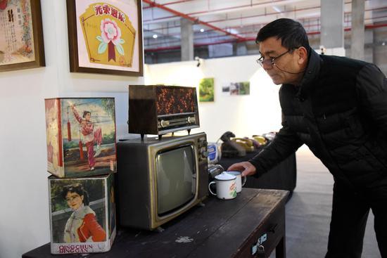 图为:一位市民在一台老式黑白电视机前驻足。 王华斌 摄