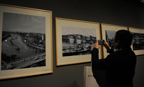 图为:多幅展出的运河老照片吸引了市民的眼光。 张茵 摄