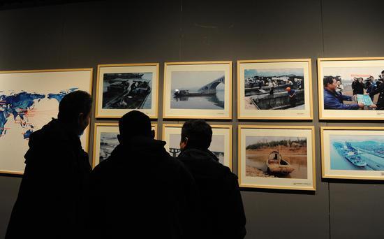 图为:三位市民在展出的图片前驻足观赏。张茵 摄