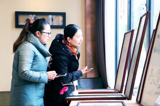 图为:女粉丝被画家叶征潮国画作品深深吸引,细细品味 小景 摄