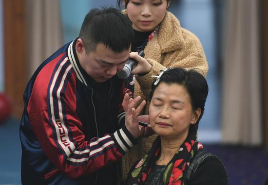 图为:化妆师为嘉宾上妆。  王刚 摄