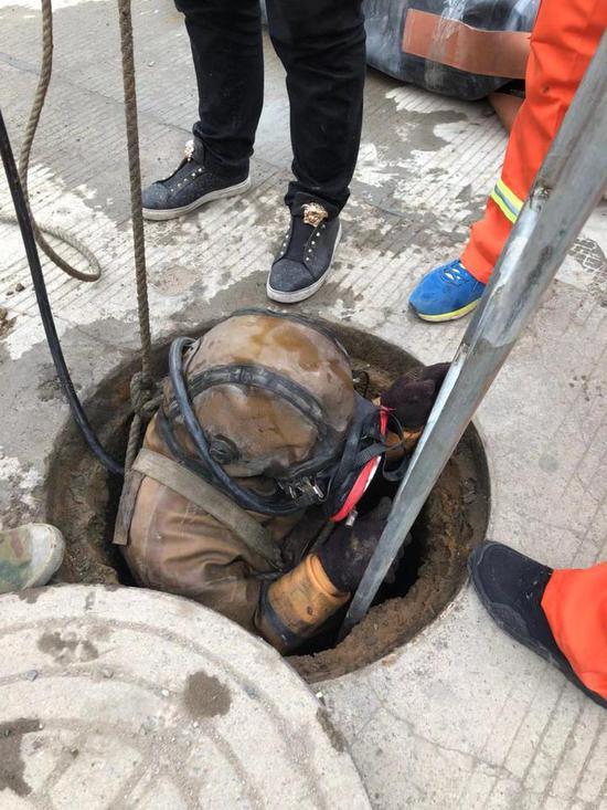 """图为:""""蛙人""""进入狭小的管道显得有些局促。临海市委宣传部提供"""
