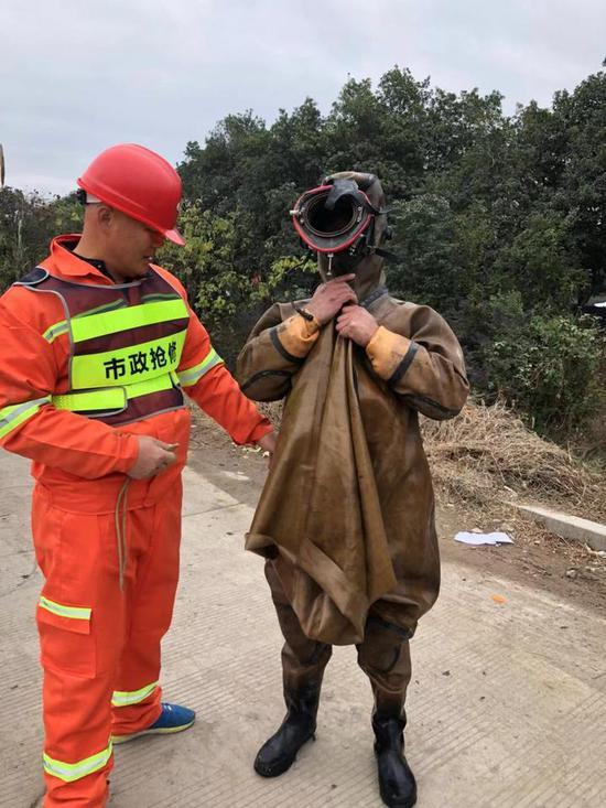"""图为:在同事的帮助下,""""蛙人""""才能穿戴、脱卸笨重的工作服。临海市委宣传部提供"""