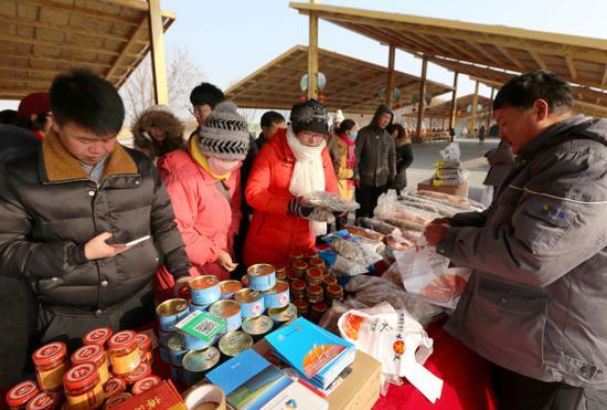 博湖县第十一届冰雪节 游客现场购买鱼制品。海潮 摄