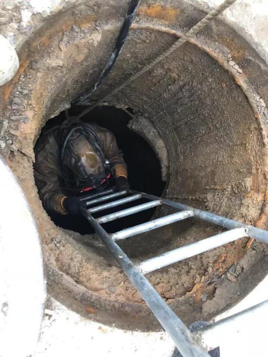 """图为:""""蛙人""""在下水道作业时仅靠一根绳子与外界联系。临海市委宣传部提供"""