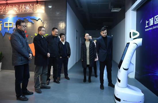 图为:浙江省委统战部副部长张润生等人在参观数字统战体验馆的智能机器人。 王刚 摄