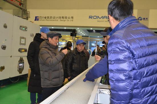 诚意药业董事长颜贻意(左1)在试机现场。 诚意药业提供