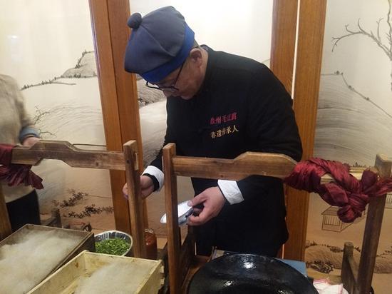 徽州毛豆腐的第六代非遗传承人蒋光明现场煎制毛豆腐。施杭 摄