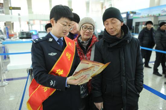图为边检民警为出入境旅客解答政策咨询。