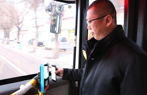 """图为伊宁市民体验""""挥卡乘车""""带来便利。刘建愉 摄"""