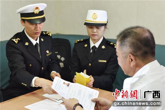 防城海关关员向船长核查船舶卫生证书和船员预防接种证书。