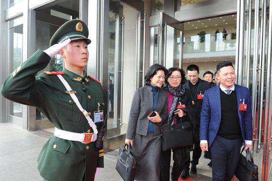 图为:会议结束后,政协委员们正步离会场。  张茵 摄