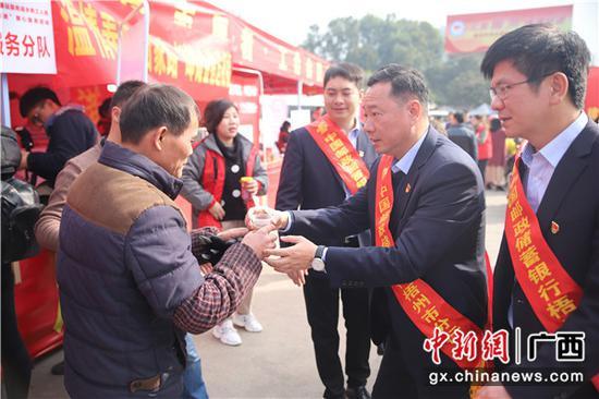邮储银行梧州市分行行长覃延宁为返乡务工人员送上热姜茶。