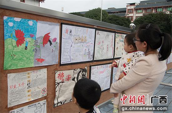 一位母亲与孩子一起观看禁毒宣传手抄报。
