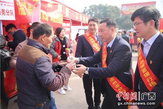 邮储银行梧州市分行志愿者为返乡务工人员送上热姜茶。