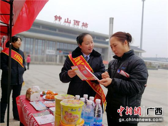 邮储银行贺州钟山县支行客户经理为返乡务工人员发放安全用卡信息。