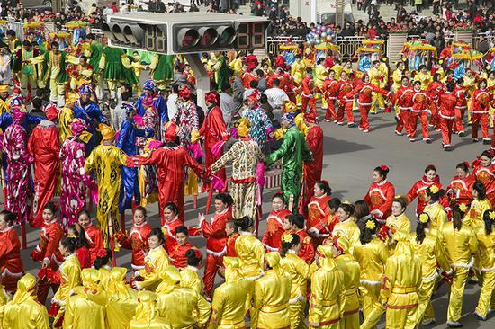 """城乡各族群众纷纷涌上街头,争相翘首一睹新年民俗""""文化大餐""""的精彩盛况,共同感受新春的欢愉和传统的年味。(摄影:买买提艾力)"""
