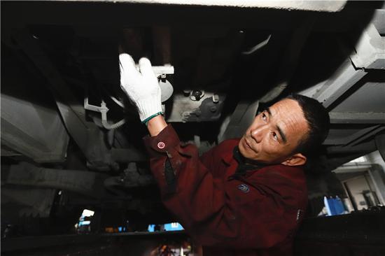 图为许益成在维修地沟里检查车辆底盘。董美巧摄