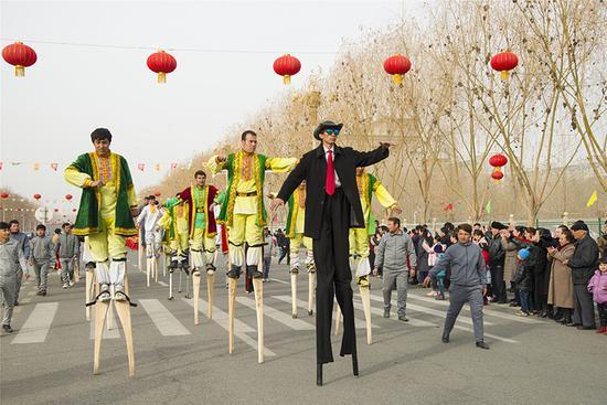 """各支表演队借助锣鼓、旱船、秧歌、舞龙、舞狮、高跷等传统表演形式,让现场观众在""""闹""""新春中尽享快乐。(摄影:买买提艾力)"""