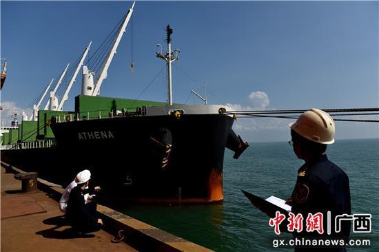 北海海关关员对载重大豆进口的船舶进行水尺计重,读取船舶水尺标志数。包拥军 摄
