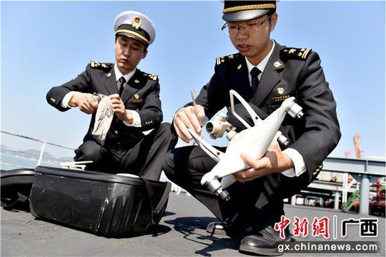 防城海关关员运正在安装用于入境船舶水尺计重的无人机。包拥军 摄