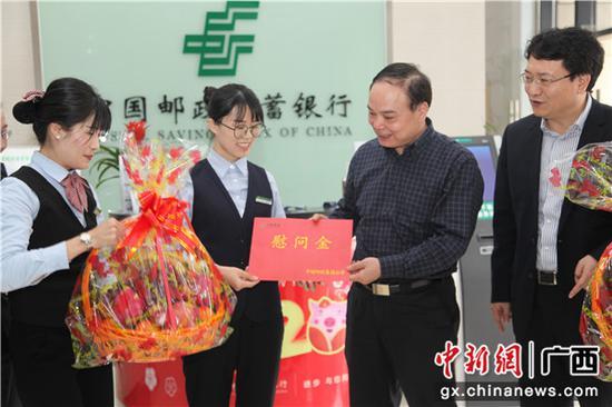 张荣林副总经理向邮储银行钦州市分行营业部送上慰问品。