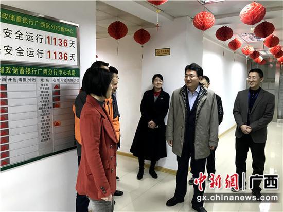 邮储银行广西区分行党委书记、行长史军保在机房与员工们亲切交谈。