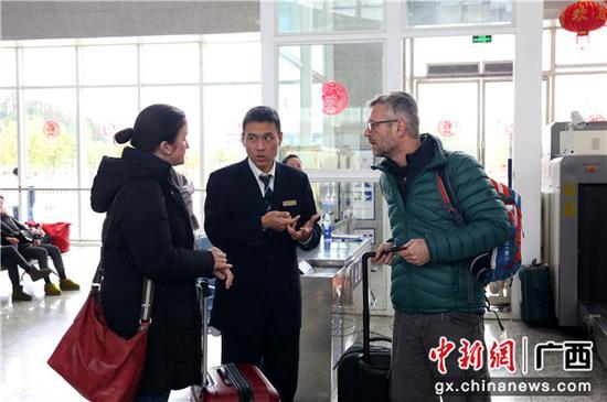 闻斌耐心为外籍旅客答疑解惑。