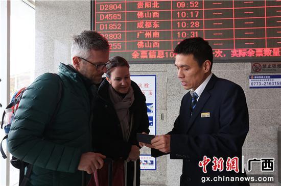 闻斌向外籍旅客提供购票咨询服务。