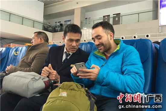 闻斌向外籍旅客介绍网络订票的方法。