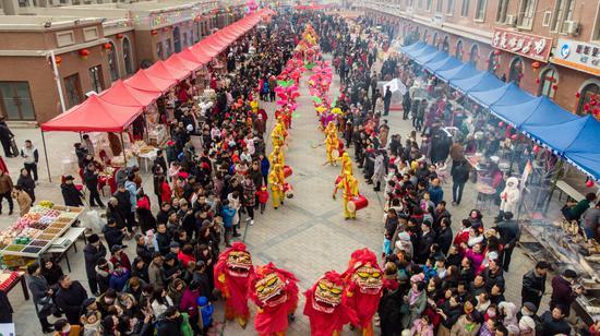 """2月19日,尉犁县举办""""激情新春 与馕共舞""""闹元宵系列活动,游客和各族群众观看社火表演。"""