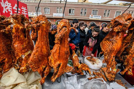"""2月19日,尉犁县举办""""激情新春 与馕共舞""""闹元宵系列活动,当地特色美食烤全羊吸引众多游客前来购买。"""