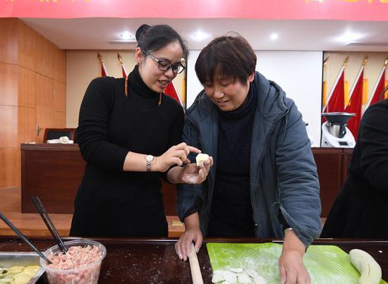 图为:两名活动参与者正在研究饺子包法。 王刚 摄