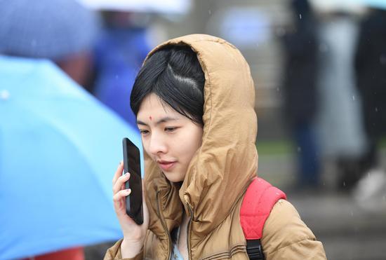 图为:一位考生冒雨打电话。   王刚 摄