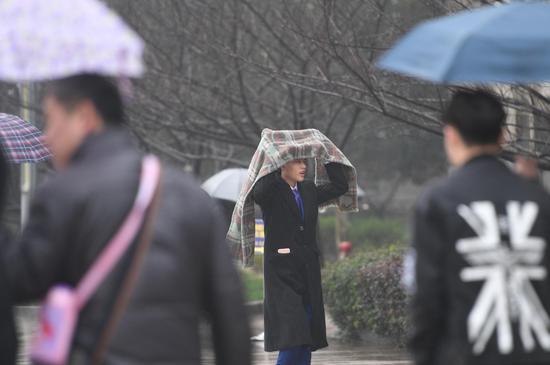 图为:一位考生冒雨进考场。   王刚 摄
