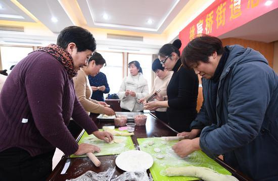 图为:多名活动参与者正在进行包饺子比赛。 王刚 摄