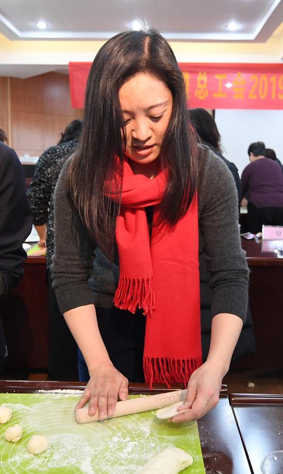 图为:一名活动参与者正在擀饺子皮。 王刚 摄
