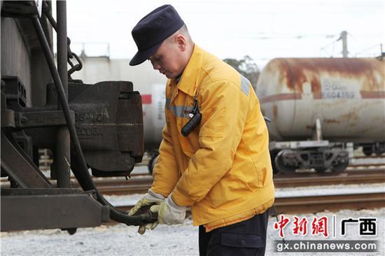 列尾作业员何庆国在连接列尾主机风管和列车制动软管。李育全 摄